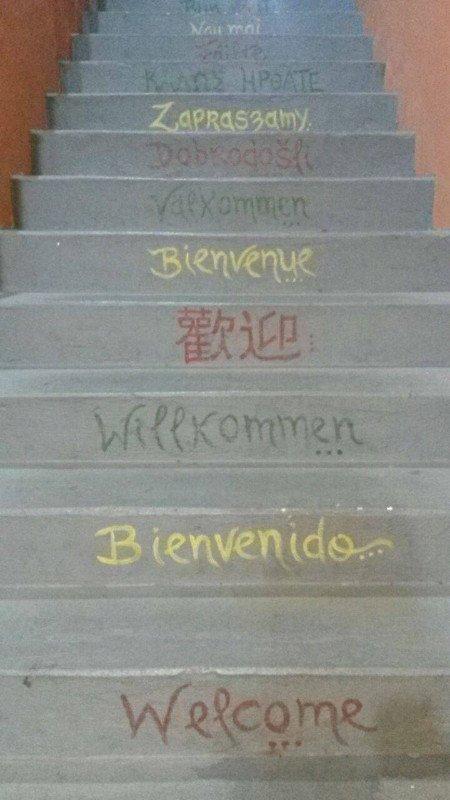 """""""Bem vindo"""" escrito em vários idiomas na escada que leva até a recepção."""